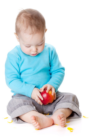 Small baby holding red apple. Isolated on white photo