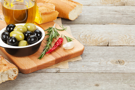 Italian food appetizer of olives, bread and spices on wooden table background with copy space Stock Photo