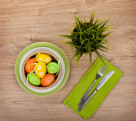 Easter eggs with silverware and potted flower over wooden table background photo