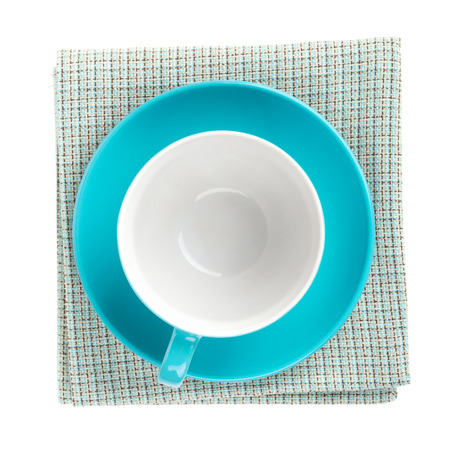 dishcloth: Blue coffee cup over kitchen towel. View from above. Isolated on white background Stock Photo
