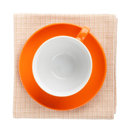 Orange coffee cup over kitchen towel. View from above. Isolated on white background photo