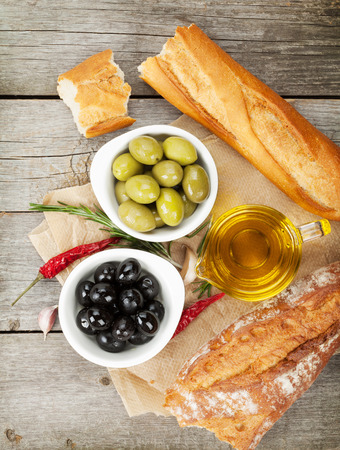 Italian food appetizer of olives, bread and spices on wooden table background photo