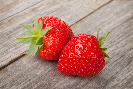 Ripe strawberries over wooden table background closeup photo