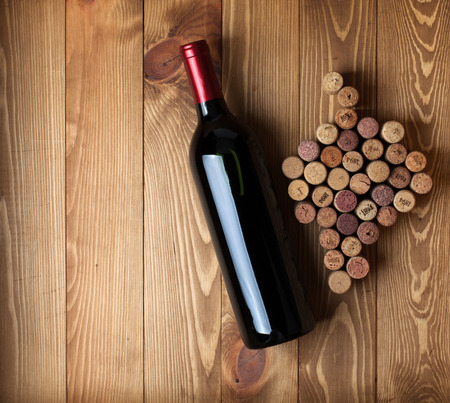 closed corks: Red wine bottle and grape shaped corks on wooden table background with copy space Stock Photo