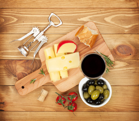 Red wine with cheese, bread, olives and spices. Over wooden table background. View from above photo