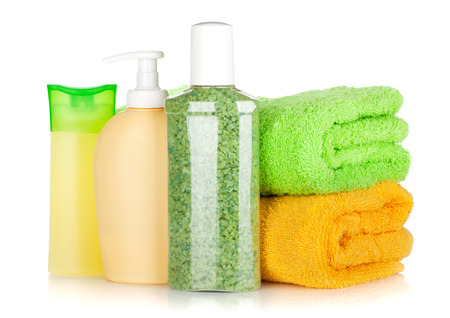 Cosmetics bottles with towels. Isolated on white background