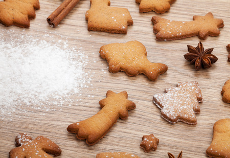 Gingerbread cookies with spices and flour over wooden table photo