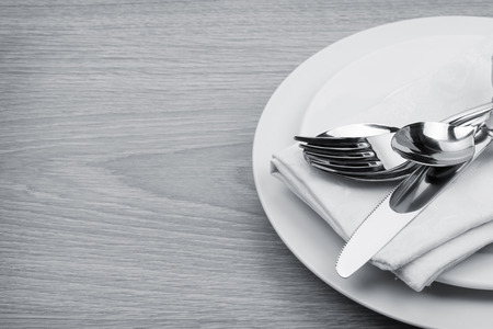 stainless steel kitchen: Silverware or flatware set of fork, spoons and knife on plates. Toned Stock Photo