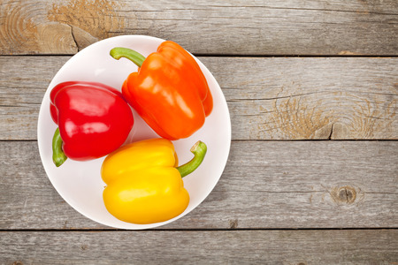 bell peppers: Colorful bell peppers on plate over wooden table background