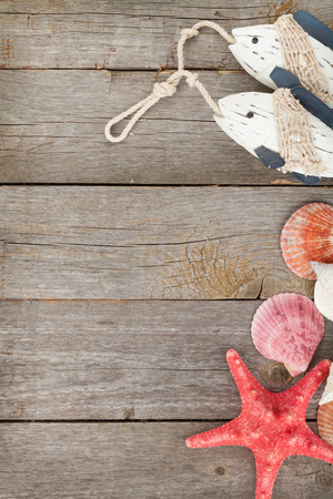 beach toys: Toy fish with seashells and starfish on a wooden background with copy space