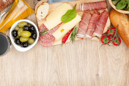 Red wine with cheese, olives, tomatoes, prosciutto, bread and spices. Over wooden table background. photo