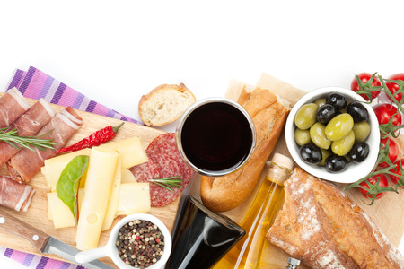 Red wine with cheese, prosciutto, bread, vegetables and spices. Isolated on white background  photo