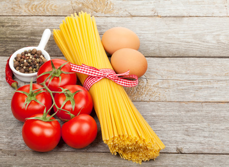 ribbon pasta: Pasta, tomatoes, eggs and spices on wooden table background Stock Photo