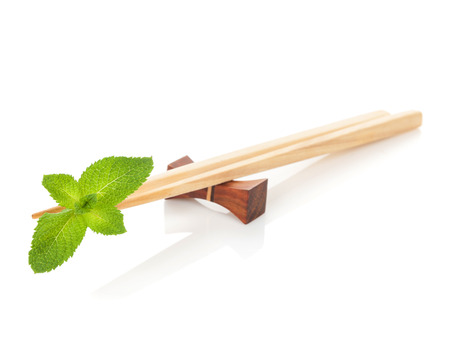 Sushi chopsticks with mint leaves. Isolated on white background photo