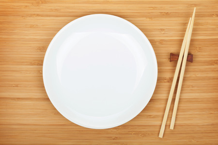 chop stick: Empty plate and sushi chopsticks on bamboo table