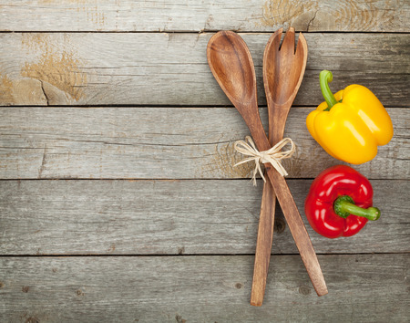 Colorful bell peppers and kitchen utensils over wooden table background   photo