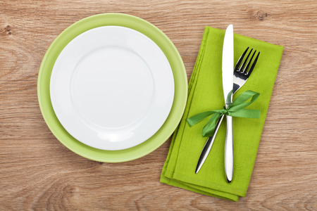 Fork with knife, blank plates and napkin. On wooden table background photo