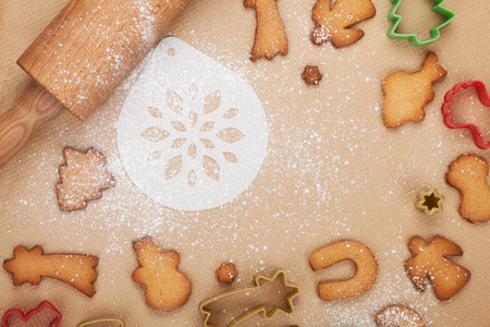 Rolling pin and gingerbread cookies on cooking paper photo