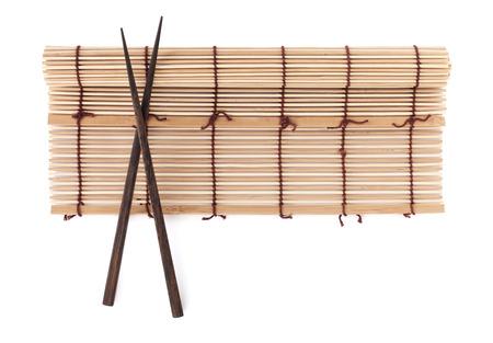Chopsticks over bamboo mat. Isolated on white background photo