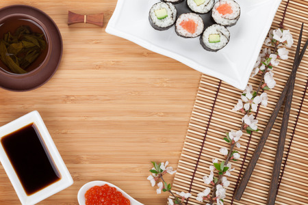 Japanese food and fresh sakura branch over bamboo table with copy space photo