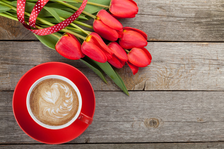 Fresh red tulips with ribbon and coffee cup with heart shape over wooden background with copy space