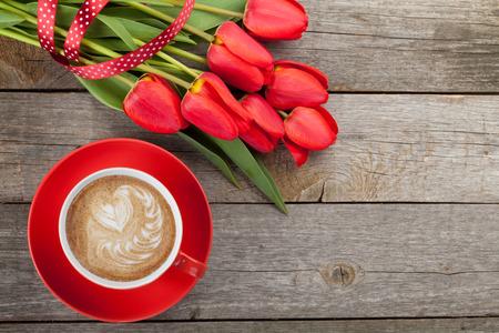 Verse rode tulpen met lint en kopje koffie met hart vorm over houten achtergrond met een kopie ruimte