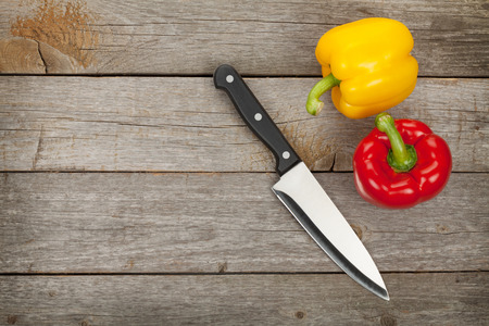 bell peppers: Colorful bell peppers and kitchen knife over wooden table background with copy space
