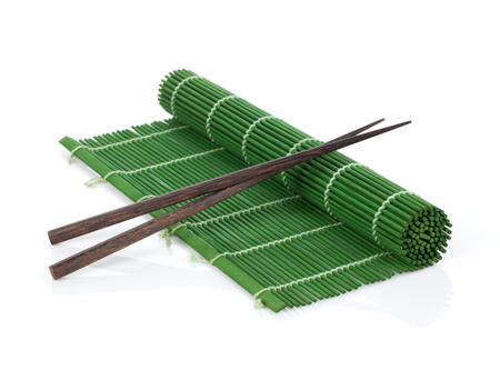Chopsticks over bamboo mat. Isolated on white background photo
