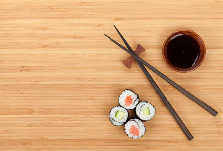 oriental cuisine: Sushi set, chopsticks and soy sauce over bamboo table with copy space Stock Photo