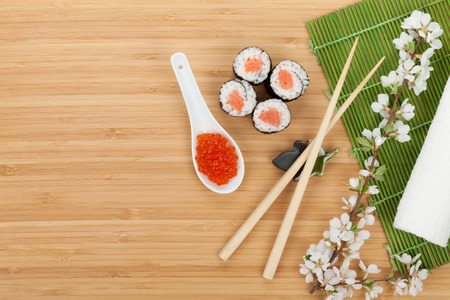 Sushi set, caviar and fresh sakura branch over bamboo table with copy space photo
