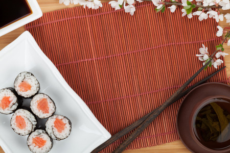 Japanese food and fresh sakura branch over mat and bamboo table with copy space photo