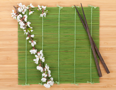 Chopsticks and sakura branch over bamboo mat. Isolated on white background photo
