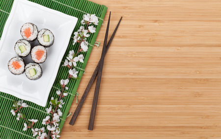 Sushi set with fresh sakura branch over bamboo table with copy space photo