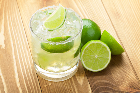 margaritas: Classic margarita cocktail with salty rim on wooden table with limes Stock Photo