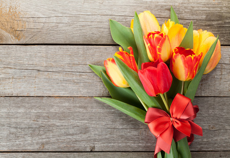 Fresh colorful tulips with ribbon and bow over wooden background with copy space photo
