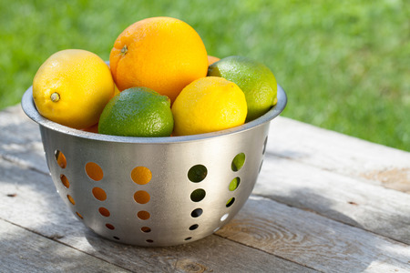 Fresh ripe citruses in colander on wood table photo