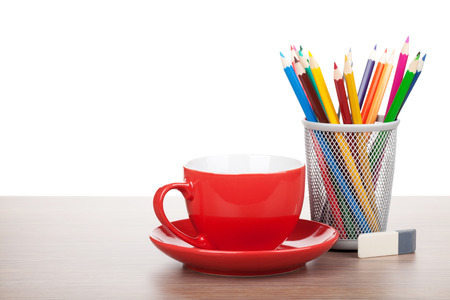 Red coffee cup and colorful pencils on wooden table photo