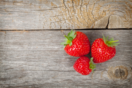Ripe strawberries over wooden table background with copy space photo
