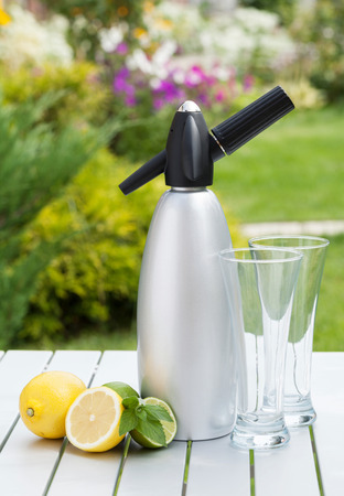 Siphon with soda, citruses and glasses for limonade photo