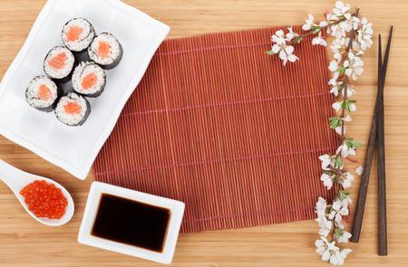 Red caviar, sushi set, sakura branch and chopsticks over bamboo table photo