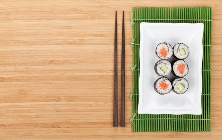 Sushi set with salmon and cucumber over bamboo table with copy space photo
