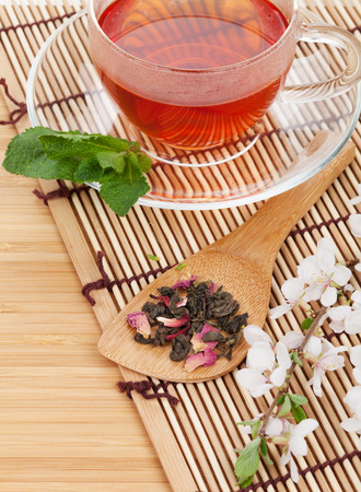 Japanese green tea and sakura branch over bamboo table with copy space photo