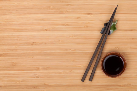 Sushi chopsticks and soy sauce bowl over bamboo table with copy space photo