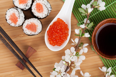 Red caviar, sushi set, sakura branch and chopsticks over bamboo table photo