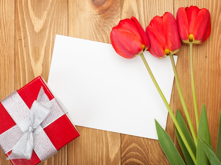 Fresh red tulips with gift box and greeting card over wooden background photo