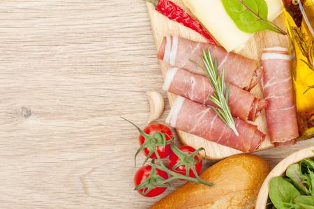 jamon y queso: Queso, jamón, pan, verduras y especias. Sobre fondo mesa de madera con copia espacio