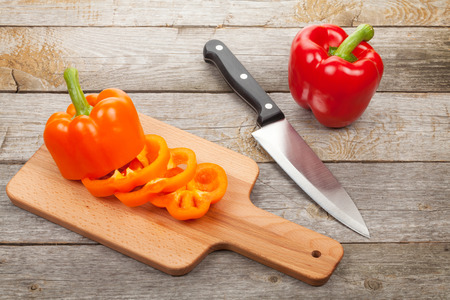 Sliced bell pepper on cutting board over wooden table photo
