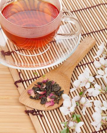 Japanese green tea and sakura branch over bamboo table photo
