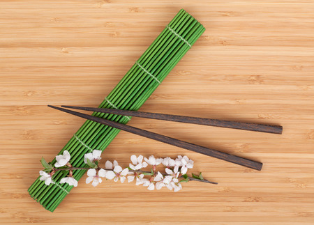 Chopsticks and sakura branch over mat on bamboo table photo