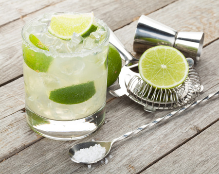 coctel margarita: Coctel clásico del margarita con borde salado en mesa de madera con limones y utensilios de bebida